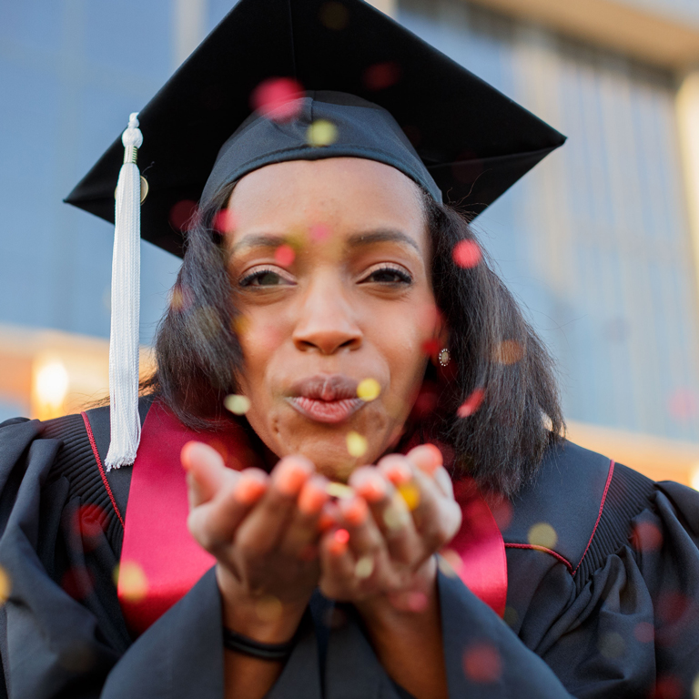 An IUPUI graduate blows confetti at the camera