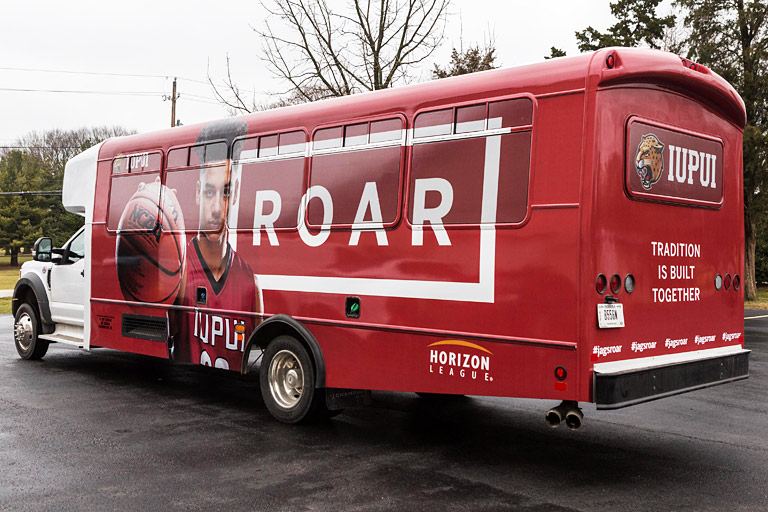 Bus wrap for the IUPUI Roar campaign with a male basketball player, the Horizon League logo, and 'Tradition is built together'