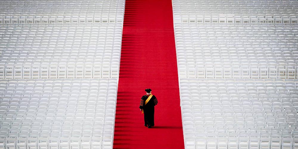 A man in a graduation robe walking away down a red isle with hundreds of empty white chairs all around.