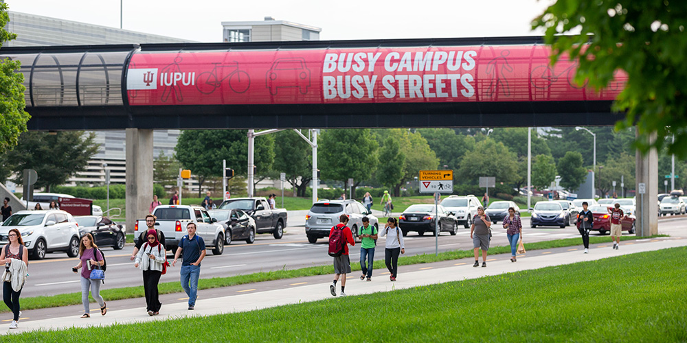"A skywalk at IUPUI with a large banner saying ""Busy Campus Busy Streets""."