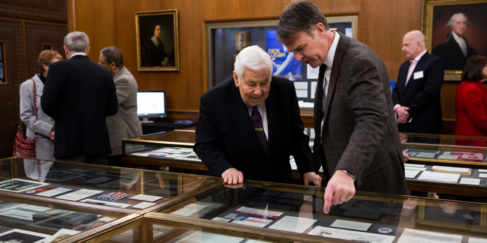 two men looking in a glass case at documents