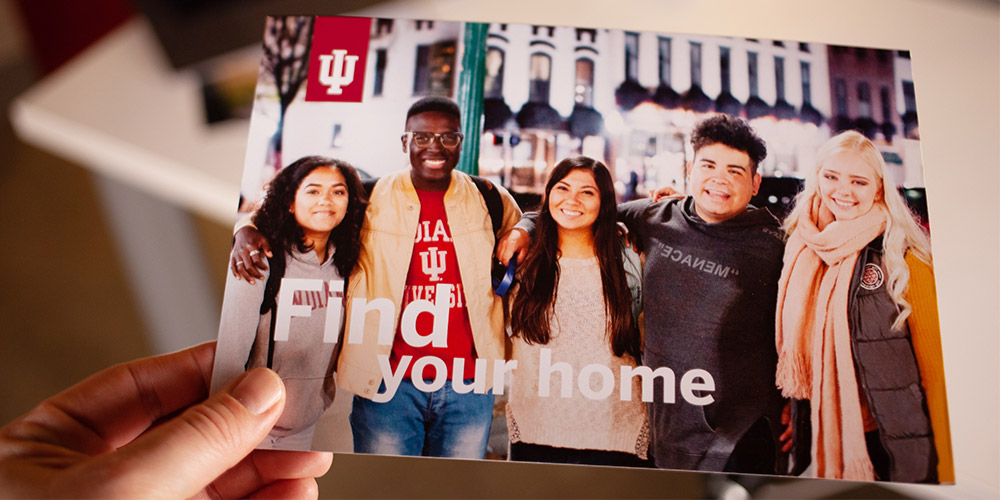 """Hand holding postcard with headline """"Find your home"""""""