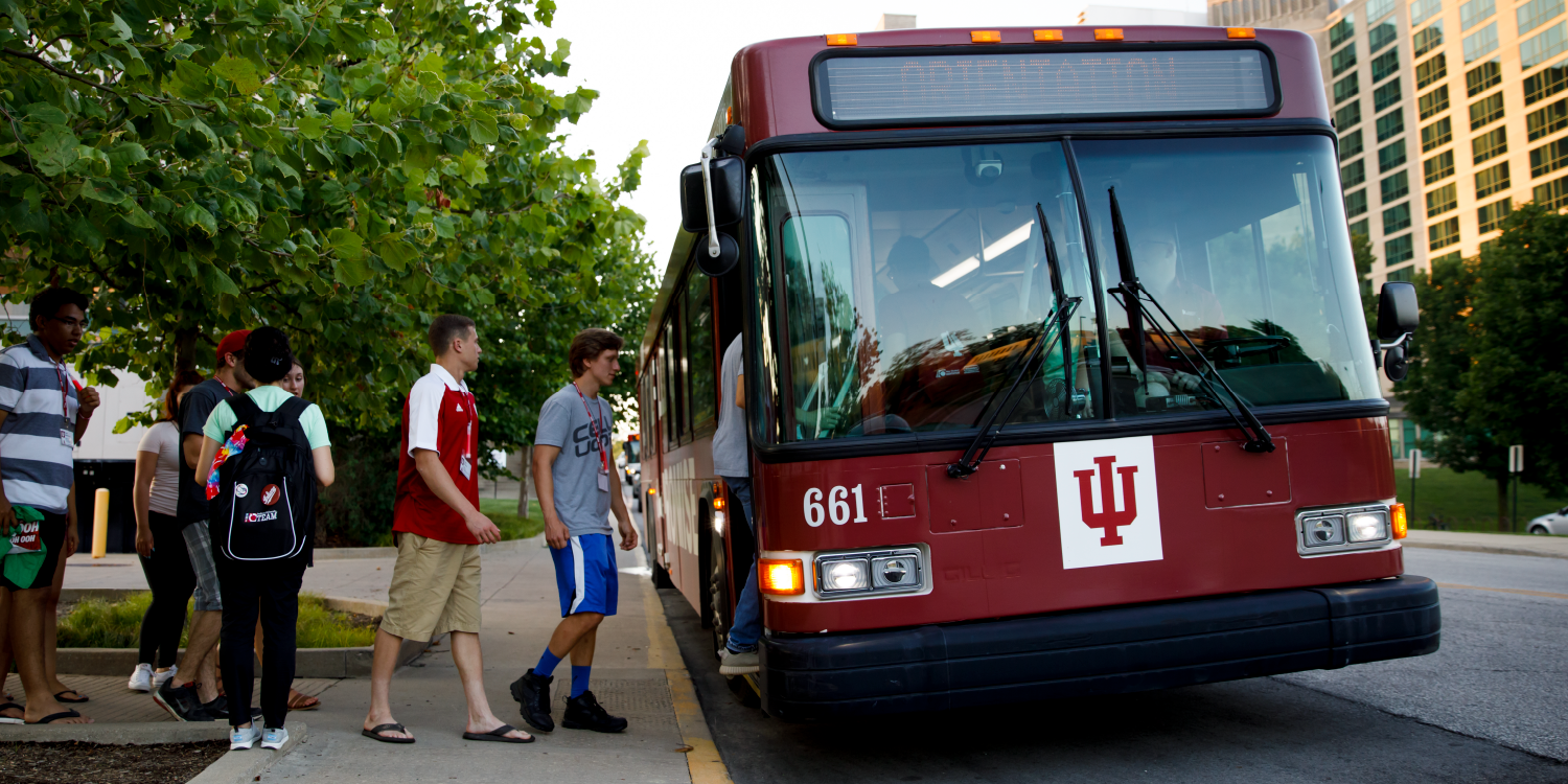 Student getting on bus with IU tab visible on front
