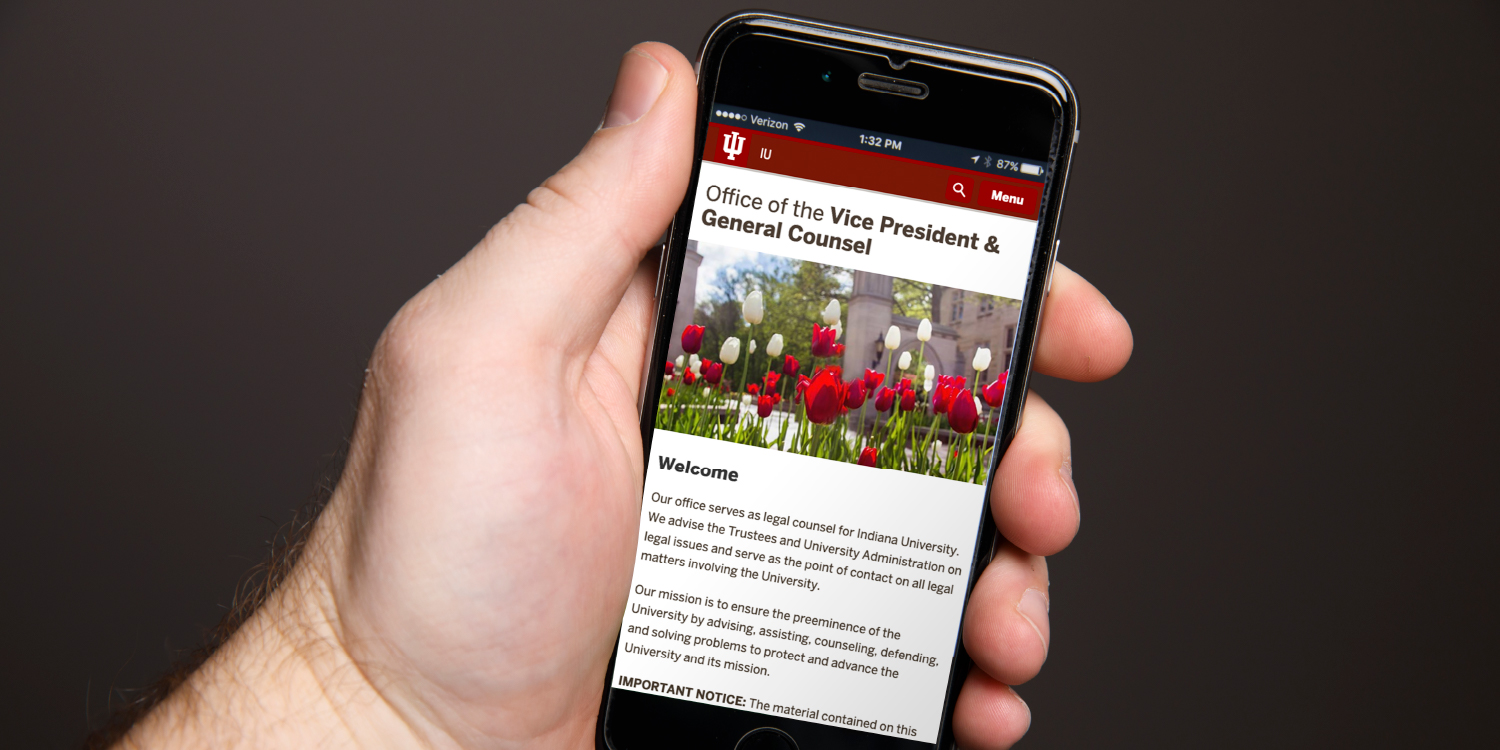 Hand holding phone showing custom webpage for Office of the Vice President & General Counsel