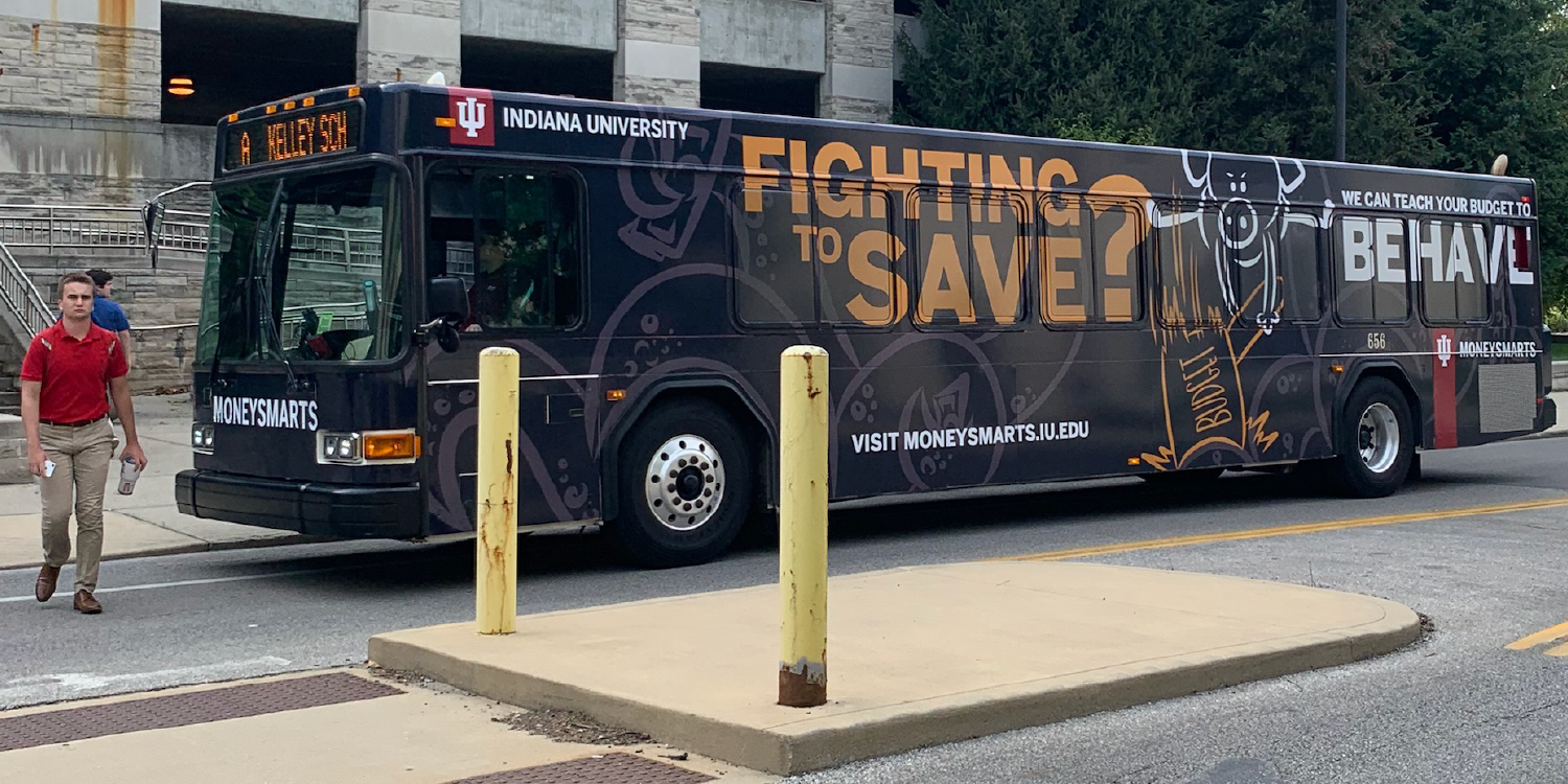 "Bus wrap for MoneySmarts program that has messaging stating ""Fighting to save?"""