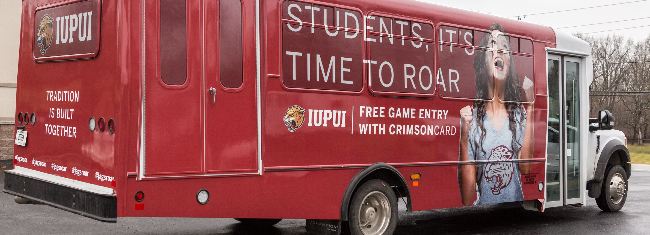 "Bus wrap of IUPUI fan and messaging that states ""Students, it's time to roar"""